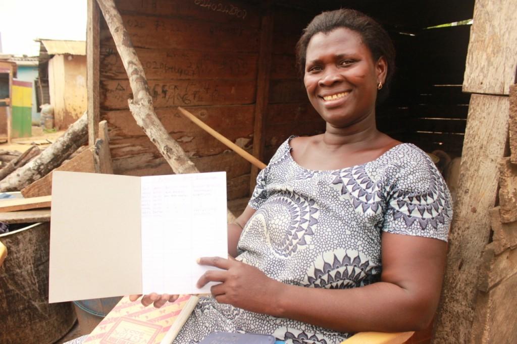Julianne Okinne, watsan committee treasurer in Abensu, demonstrates the watsan's recordkeeping as part of their commitment the community borehole.